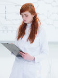 Student taking notes in lab Stock Photography