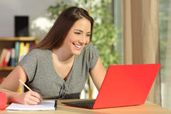 Student taking notes and learning with a laptop. Student taking notes and learning on line with a red laptop sitting in a table in the living room at home Royalty Free Stock Image