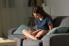 Student taking notes in the night at home. Full body portrait of a student taking notes in the night sitting on a couch in the living room at home Stock Images