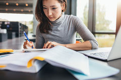 Student taking notes from textbook. Close up image of a young female student doing assignments in library. Asian woman taking notes from textbook Royalty Free Stock Photography