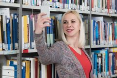 Student Taking Selfies am Telefon in der Bibliothek Stockfoto