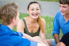 Student talking having picnic at river Stock Photo
