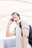 Student talking on phone in airport Royalty Free Stock Photo
