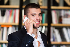 Student talking on the phone in the library. Student in library Royalty Free Stock Image
