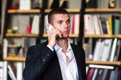 Student talking on the phone in the library. Student in library Royalty Free Stock Photo