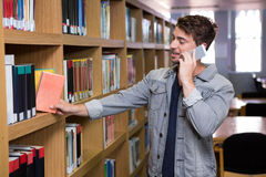 Student talking on the phone in library. At the university Royalty Free Stock Photography