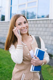 Student talking on phone and looking at camera. Student talking on her phone and looking at camera royalty free stock images