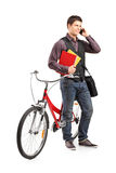 Student talking on phone and standing by a bike. Full length portrait of a student talking on phone and standing by a bike isolated on white background Stock Photos