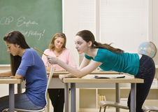 Student tapping classmate in classroom Royalty Free Stock Image