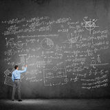 Student or teacher at blackboard. Rear view of man drawing formulas on blackboard with chalk Royalty Free Stock Photos