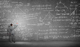 Student or teacher at blackboard. Rear view of man drawing formulas on blackboard with chalk Royalty Free Stock Photography