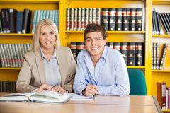 Student And Teacher With Books Sitting At Table In. Portrait of confident male student and teacher with books sitting together at table in college library Stock Photography