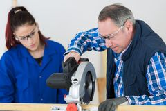 Student and teacher in carpentry class using circular saw. Circular royalty free stock photography