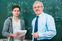 Student with a teacher in classroom. Male student with a teacher in classroom Stock Photos