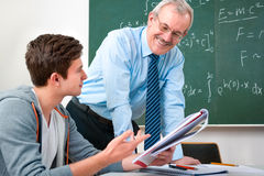Student with a teacher in classroom. Male student with a teacher in classroom Stock Images