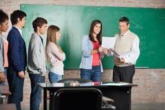 Student And Teacher Looking bij Testresultaat binnen Stock Afbeeldingen