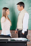 Student And Teacher Looking At Each Other In. Side view of young college student and teacher looking at each other against greenboard in classroom Stock Photography