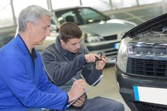 Student and teacher mechanics changing car headlight in workshop Royalty Free Stock Image