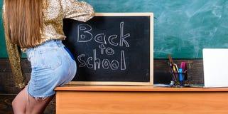 Student teacher mini skirt buttocks sit table blackboard inscription back to school. Girl denim skirt breaking. School clothing rules. School dress code. Back stock photos