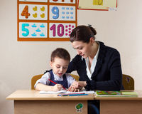 Student and teacher. Teacher teaches a young child at a school desk Royalty Free Stock Image