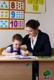 Student and teacher. Teacher teaches a young child at a school desk Stock Photos