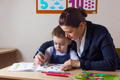 Student and teacher. Teacher teaches a young child at a school desk Royalty Free Stock Photos