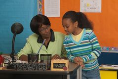 Student at teachers desk. A teacher reviews a students work stock photography