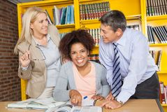Student With Teachers Looking At Each Other In. Portrait of cheerful female student with teachers looking at each other in university library Royalty Free Stock Image