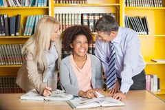 Student With Teachers In University Library. Cheerful college student with teachers in university library stock photography