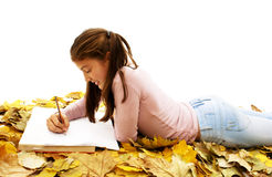Student teenage girl lying down with leaves around Royalty Free Stock Photo
