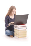 Student teenage girl sitting sideways on the book with laptop Stock Photos