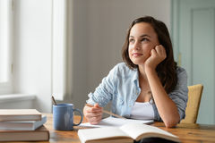 Student teenage girl studying at home daydreaming Stock Images