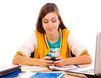Student text messaging on cell phone. At desk Stock Images