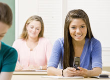 Student text messaging on cell phone in classroom Stock Photo