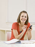 Student text messaging on cell phone in classroom Royalty Free Stock Photo
