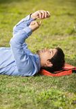 Student Text Messaging On Mobilephone While Lying. Side view of male student text messaging on mobilephone while lying on grass at university campus Royalty Free Stock Photos