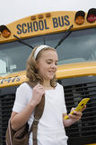 Student Text Messaging By School Bus Stock Image