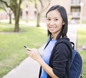 Student texting. An asian  girl texting on the phone in campus Royalty Free Stock Photos