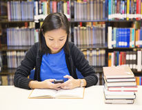 Student texting. Smiling asian woman  in library texting Stock Photography