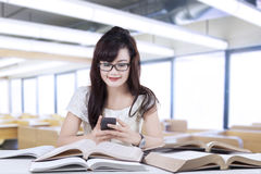 Student texting while studying Royalty Free Stock Image