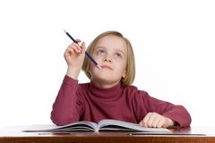Student thinking. Girl at a school desk, isolated on a white background Stock Photos