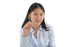 Student Thinking. Female college student holding ink pen and pondering a question royalty free stock image