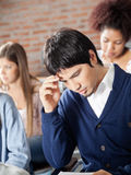 Student Thinking With Classmates In Classroom Stock Photos
