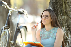 Student thinking sitting in a park Stock Photos