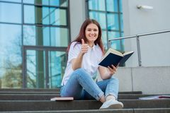 Student thumb up gesture. Smiling university student with thumb up gesture outdoors on Campus sitting on stairs holding books. A confident student holding books royalty free stock image