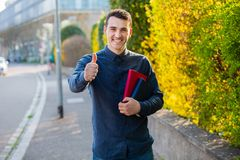 Student thumb up. University. Smiling young student man holding thumb up and books on a university background. Confident young smiling student with thumb up stock image