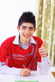 Student thumbs up. Smiling teenage guy writing an exam makes thumbs up sign Royalty Free Stock Photos