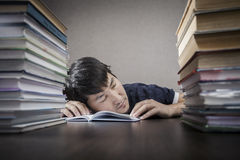The student and time behind textbooks. The young man sleep on a table between textbooks Stock Photo