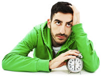 Student tired hold clock, sitting at the desk, looking up. royalty free stock image