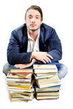Student tired of studying on piles of books. Handsome college student tired on piles of books, isolated on white Stock Image